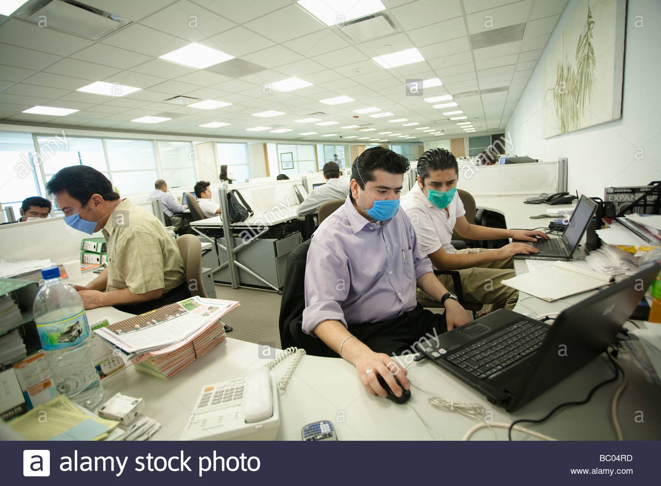 some-people-work-at-their-computers-wearing-masks-inside-an-office-BC04RD.jpg